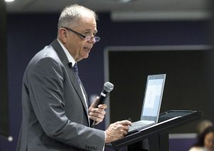 A man, Professor Hal Swerissen, stands with a microphone in his hand in front of a laptop.