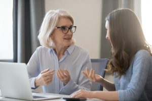 Old woman consulting with person at desk