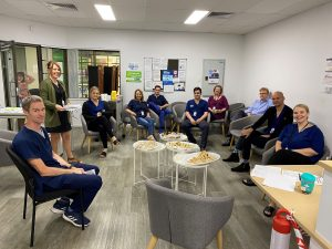 A group of people sit in a half circle. Many of them are wearing scrubs.