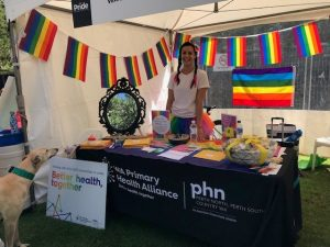 A woman stands at a stall. The LGBTI flag covers teh stall.